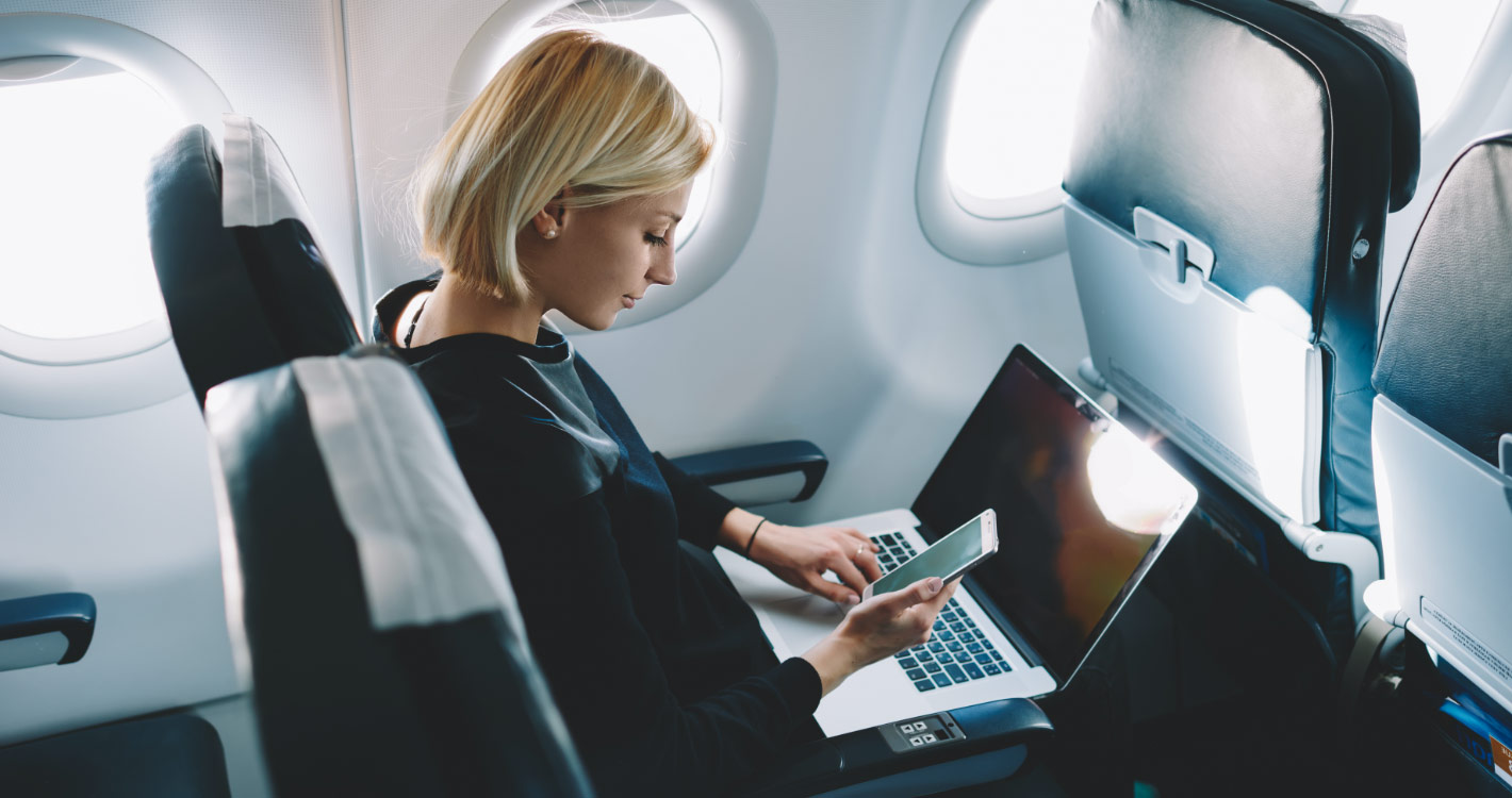 Woman on a plane using mobile devices