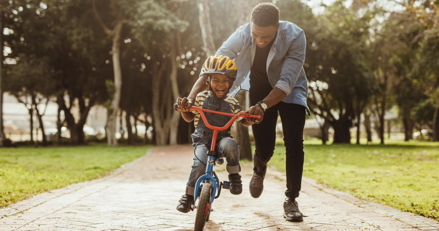 Dad teaching kid how to ride a bikecycle